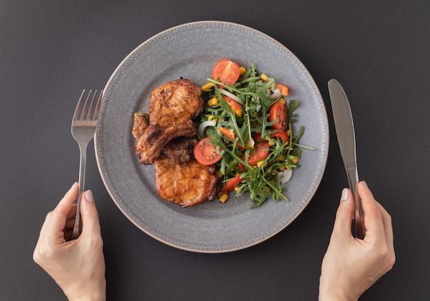 Vrouw handen met mes en vork voorbereiden om te proeven van de heerlijke gebakken varkensribbetjes met verse groentesalade bovenaanzicht