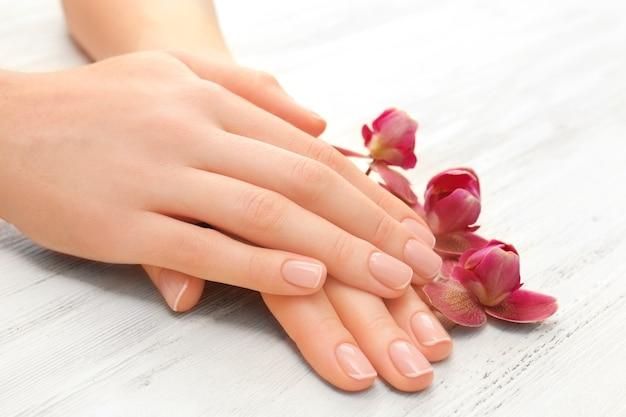 Vrouw handen met mooie manicure en paarse orchidee op houten achtergrond, close-up
