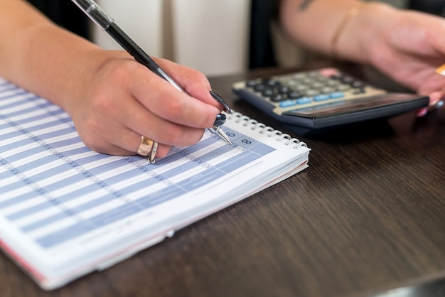 Vrouw handen met pen en planner op receptie tafel