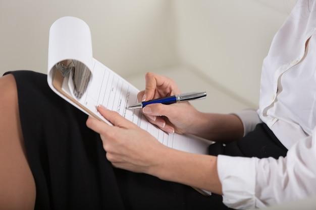 Vrouw handen met pen ondertekening document, close-up