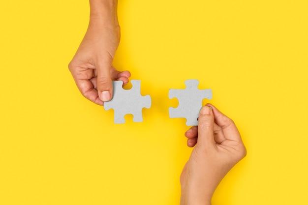 Vrouw handen met puzzelstukjes op een gele achtergrond