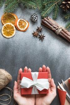 Vrouw handen met rode ingepakte geschenkdoos met lint, takje naaldboom, kegel, inpakpapier, schaar, kaneelstokjes, plakjes sinaasappel op zwarte ondergrond
