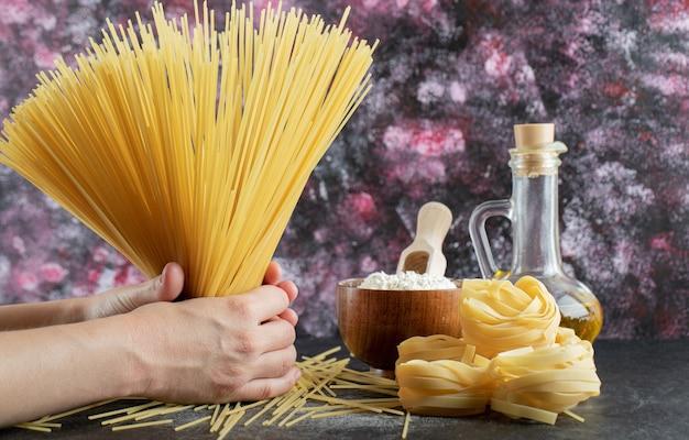 Vrouw handen met spaghetti op kleurrijk met olie en bloem.