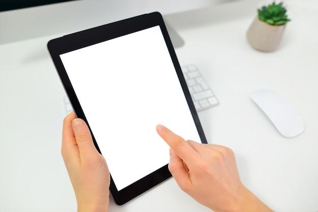 Vrouw handen met tablet pc-computer met geïsoleerde scherm op bureau.