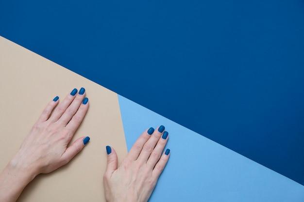 Vrouw handen met trendy blauwe nagels op geometrische blauw en beige