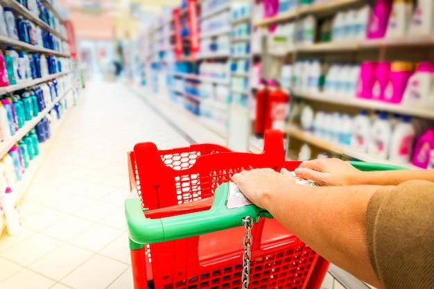 Vrouw handen met winkelwagentje close-up, planken met goederen op de achtergrond, afgezwakt