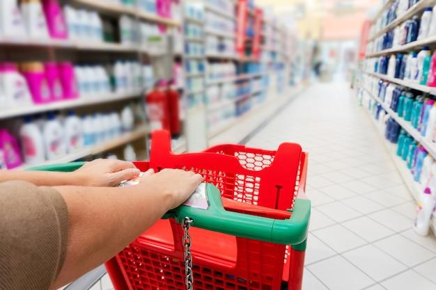 Vrouw handen met winkelwagentje close-up, planken met goederen op de achtergrond