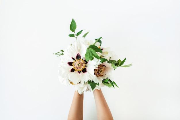 Vrouw handen met witte pioenrozen bloemen op witte ondergrond