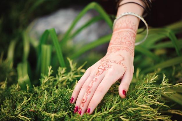 Vrouw handen met zwarte mehndi tattoo. handen van indiase bruid meisje met zwarte henna tatoeages. mode. india