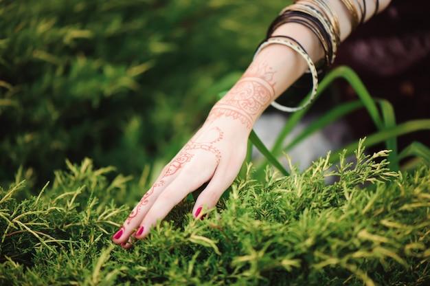 Vrouw handen met zwarte mehndi tattoo. handen van indiase bruid vrouw met zwarte henna tatoeages. mode. india