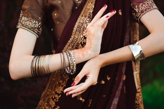 Vrouw handen met zwarte mehndi tattoo. handen van indiase bruid vrouw met zwarte henna tatoeages. mode.