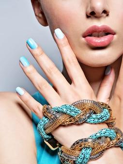 Vrouw handen nagels manicure mode blauwe sieraden.