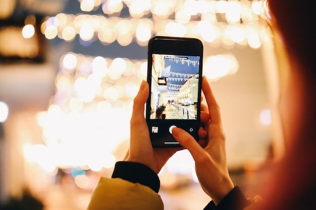 Vrouw handen nemen foto van nacht stadslichten met een smartphone