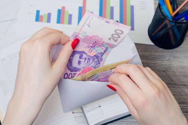 Vrouw handen nemen salaris uit een envelop