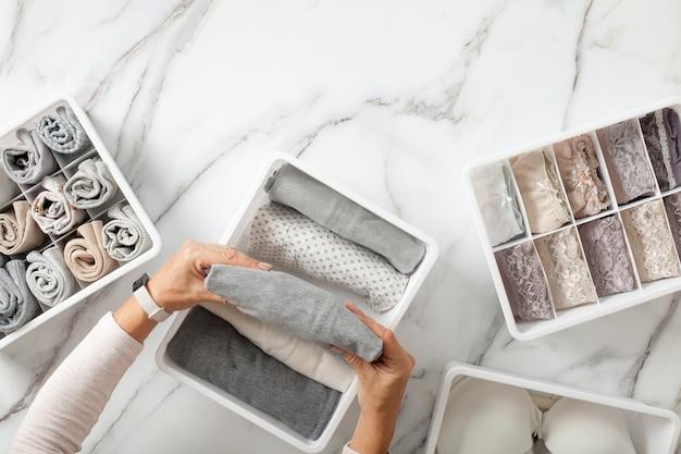 Vrouw handen netjes vouwen ondergoed en sorteren in lade-organisatoren op witte marmeren achtergrond