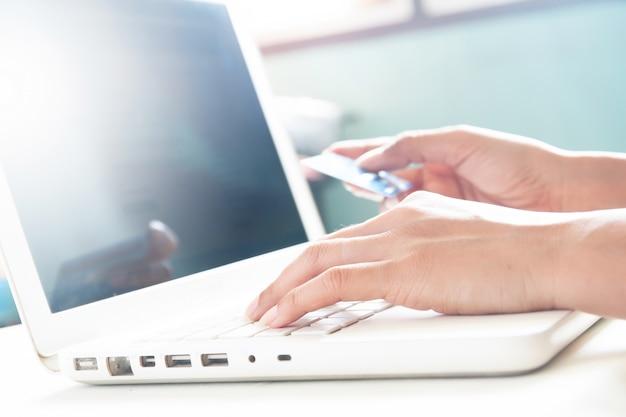 Vrouw handen op toetsenbord van laptop en bedrijf creditcard, online winkelen concept met kopie ruimte