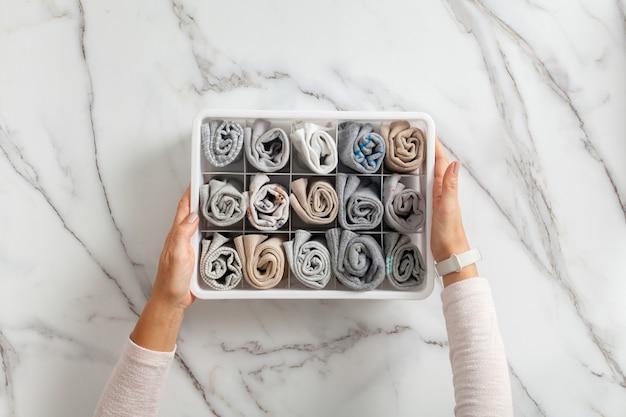 Vrouw handen plaatsen organizer ladeverdeler met vol gevouwen ondergoed en sokken