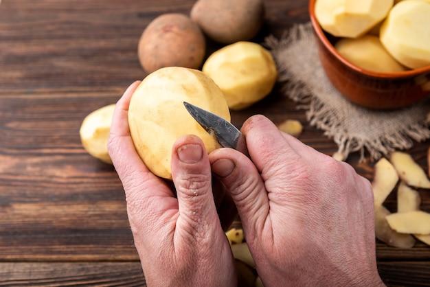 Vrouw handen schillen aardappel. maak aardappelen op een houten oppervlak schoon. voedsel repareren om te koken.