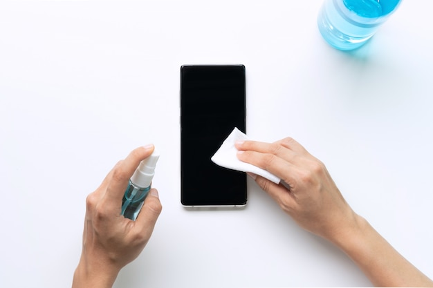 Vrouw handen schoonmaken smartphone met desinfecterende natte doekjes en alcohol spray.