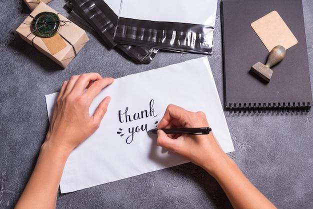 Vrouw handen schrijven dank u tekst op polyethyleen envelop