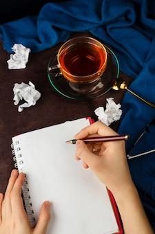 Vrouw handen schrijven op een notitieblok met blanco pagina met krap papier, glazen en kopje thee
