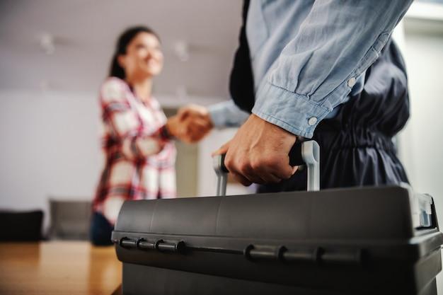 Vrouw handen schudden met een reparateur terwijl thuis.