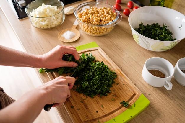 Vrouw handen, snijden uien