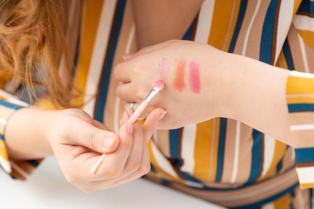 Vrouw handen testen make-up lippenstift kleuren op haar hand