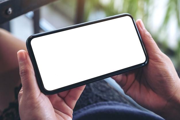 Vrouw handen vasthouden en gebruiken van een zwarte mobiele telefoon met een leeg scherm horizontaal om te kijken