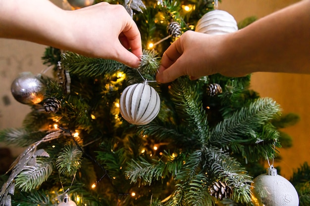 Vrouw handen versieren kerstboom. kerstboom met witte en zilveren versieringen, ornamenten speelgoed en bal. interieur in moderne klassieke stijl. kerstavond thuis, tijd voor feest.