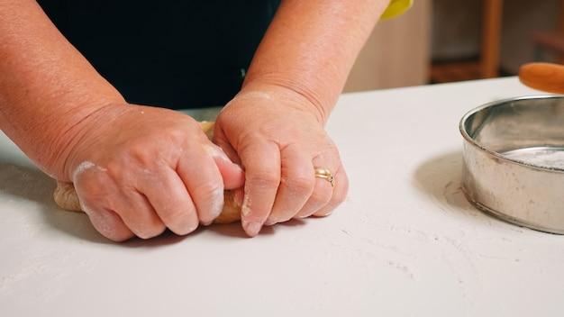 Vrouw handen vormen brood in de buurt van keukengerei bestrooid met bloem tafel. gepensioneerde oudere bakker met bonete die ingrediënten mengt met gezeefd tarwemeel kneden voor het bakken van traditionele cake, brood