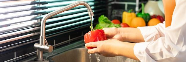 Vrouw handen wassen groenten voor de bereiding van veganistische salade