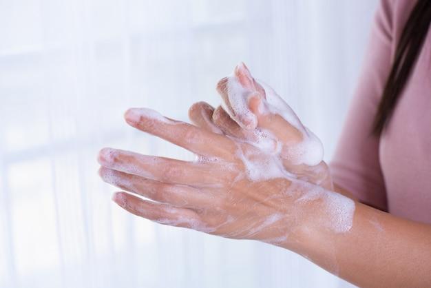 Vrouw handen wassen met zeep ter voorkoming van coronavirusziekte (covid-19)