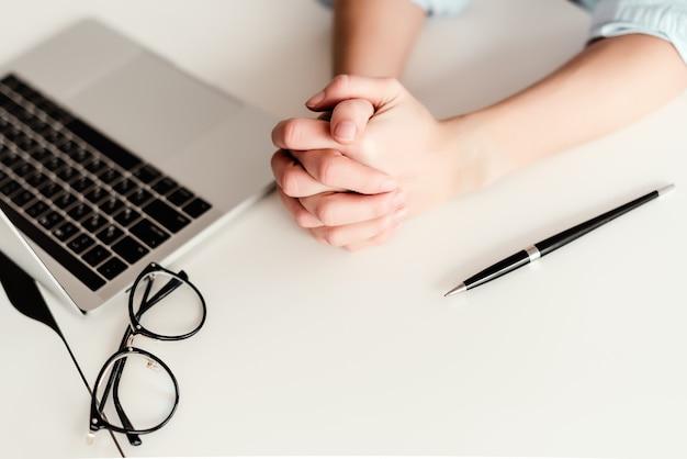 Vrouw handen werken achter de laptop op het bureau in het kantoor