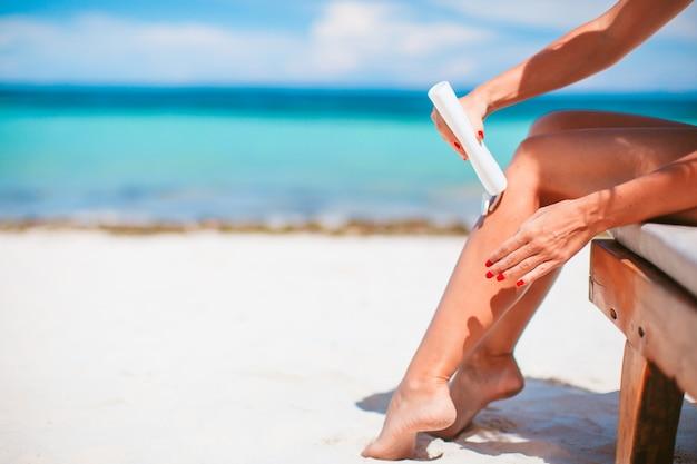 Vrouw handen zetten zonnebrandcrème uit een fles zonnebrandcrème achtergrond de zee