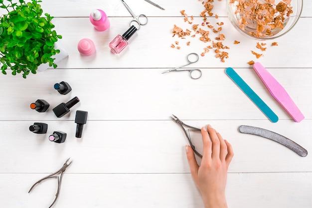 Vrouw handen zorg. bovenaanzicht van mooie gladde vrouw handen met professionele nagelverzorging tools voor manicure op witte achtergrond. detailopname. bovenaanzicht. ruimte kopiëren