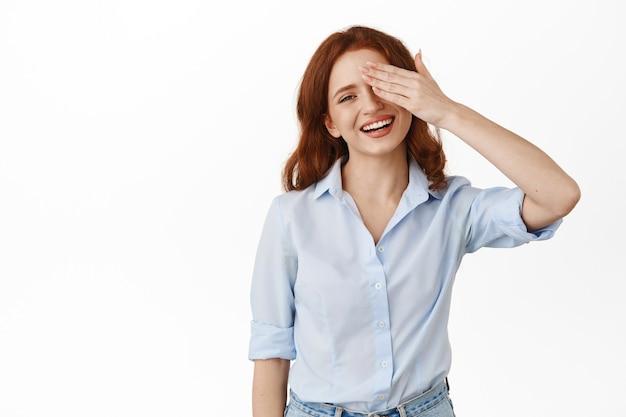 Vrouw hapt naar adem van verbazing, verbergt de ene helft van haar gezicht met handpalm, starend naar iets geweldigs, staande in blouse op wit