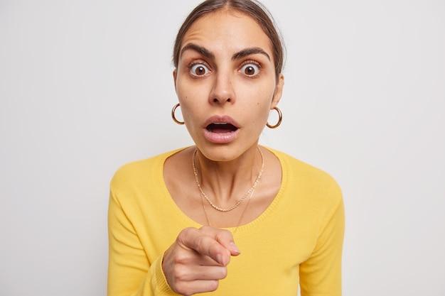 Vrouw hapt van verbazing wijst direct naar camera met wijsvinger houdt adem in van verbazing draagt casual gele trui op wit realiseert zich wie schuldig is
