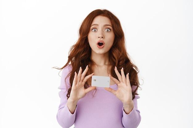Vrouw hapt verbaasd naar adem, laat creditcard zien en zegt wow, verbaasd starend, groot nieuws vertellend, staande op wit