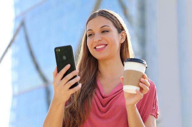 Vrouw hebben videogesprek met smartphone terwijl ze een kopje koffie vasthoudt