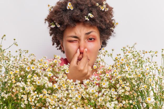 Vrouw heeft ademhalingsproblemen houdt neus vast heeft last van allergie voor kamille houdt grote bos bloemen vast heeft rode jeukende ogen