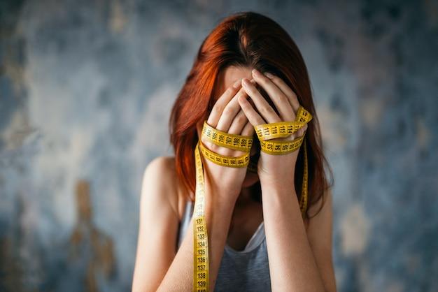 Vrouw heeft betrekking op gezicht met haar handen vastgebonden met een meetlint. vet of calorieën verbranden concept. gewichtsverlies