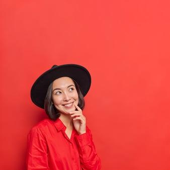 Vrouw heeft blije gezichtsuitdrukking houdt hand op gezicht gefocust boven gekleed in modieuze outfit poseert op levendig rood