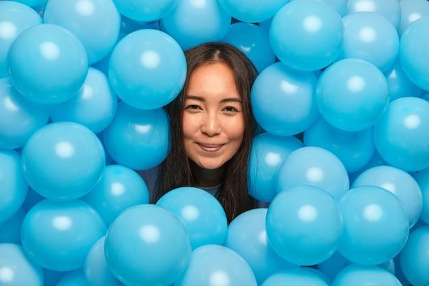 Vrouw heeft blije uitdrukking geniet van feestelijke gebeurtenis omringd met opgeblazen blauwe ballonnen