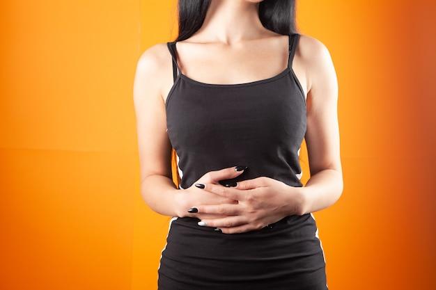 Vrouw heeft buikpijn op oranje achtergrond