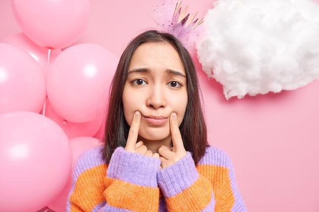 Vrouw heeft donker haar maakt een glimlach met vingers die in een slecht humeur zijn op verjaardagsfeestje draagt prinsessenkroon op het hoofd warme trui poses