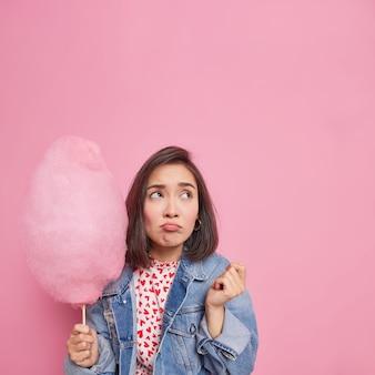 Vrouw heeft een droevige, peinzende uitdrukking boven gericht houdt lekkere suikerspin op stok heeft een slecht humeur