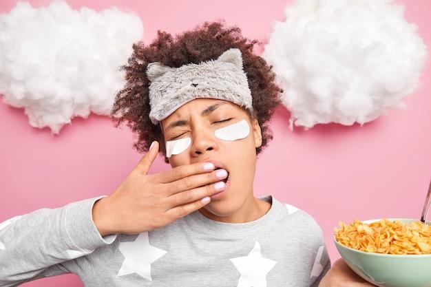 Vrouw heeft een hekel aan vroeg wakker worden gaapt tegens mond met hand gekleed in slaappak slaapmasker op voorhoofd houdt kom ontbijtgranen vast