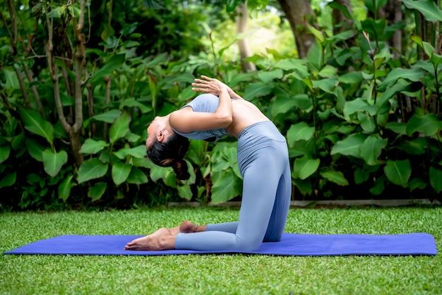 Vrouw heeft een mooi lichaam, yoga doet in een elegante houding, in het groene park