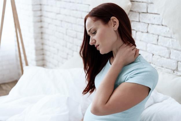 Vrouw heeft een pijnlijke nek. ze voelt zich slecht. een grimas op zijn gezicht.